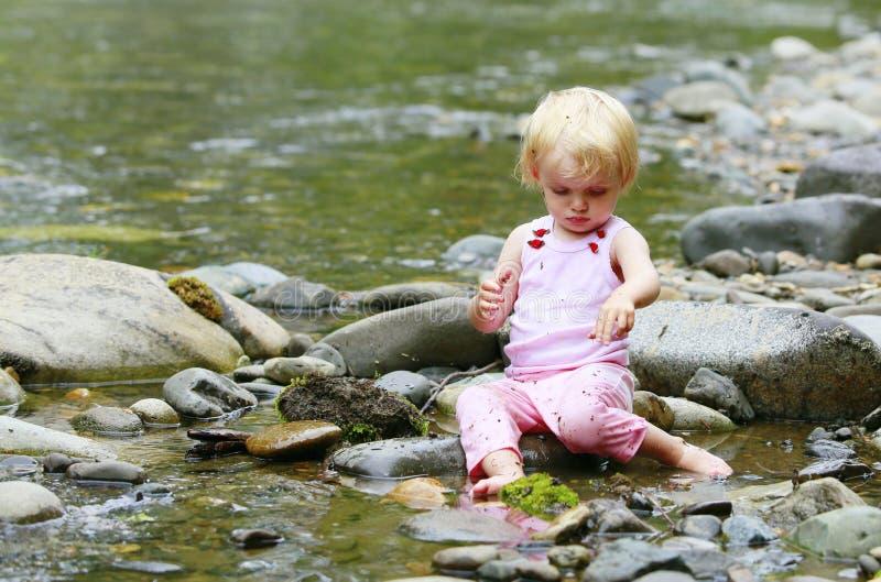 Niña sucia en un traje rosado que se sienta en las rocas en el río foto de archivo