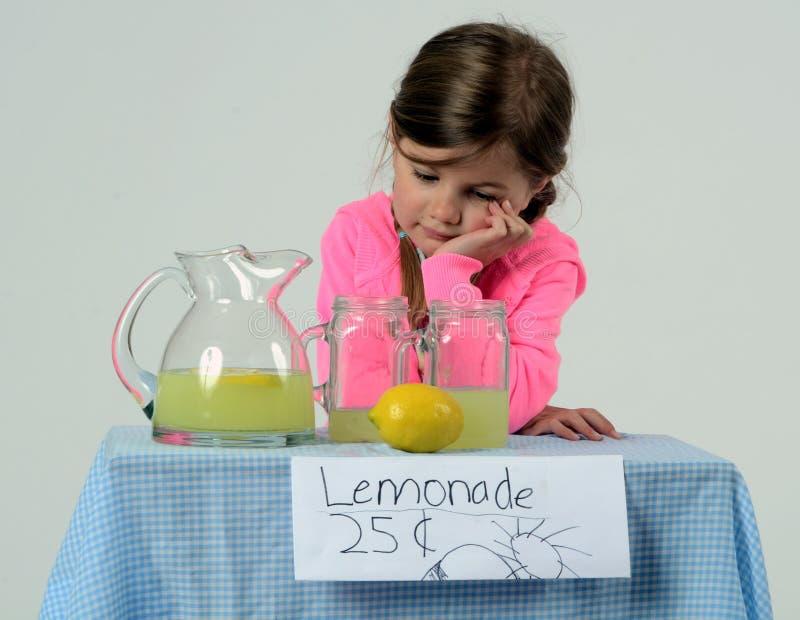 Niña triste en el soporte de limonada en verano fotografía de archivo