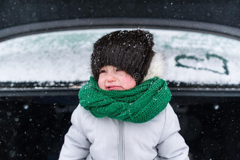 Niña triste en la ropa caliente que se coloca en el tronco abierto del coche en invierno fotografía de archivo