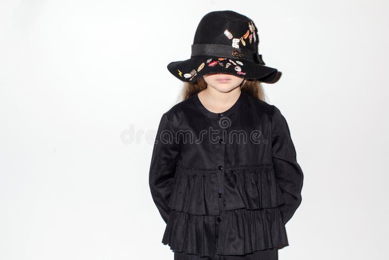 Niña triste en pared blanca permanente del sombrero negro fotografía de archivo