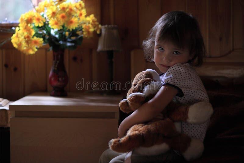 Niña triste que abraza el oso de peluche foto de archivo