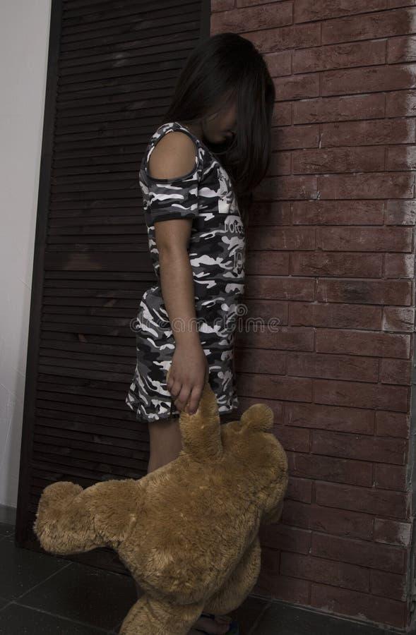 Niña triste que abraza su oso de peluche muchacha castigada que coloca la pared de ladrillo cercana foto de archivo