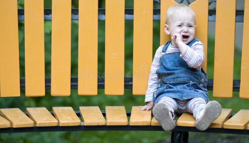 Niña triste que se sienta solamente en un banco. fotos de archivo libres de regalías