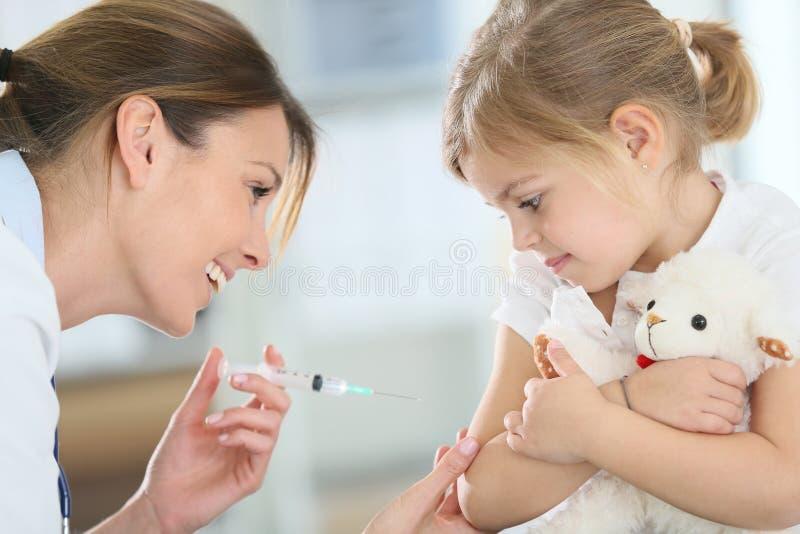 Niña valiente que recibe la inyección del doctor imagenes de archivo