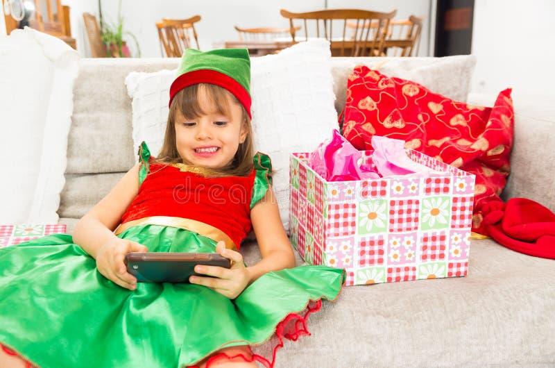 Niña vestida como tenencia del duende de la Navidad fotos de archivo