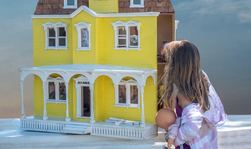 Niña y casa de muñecas imagenes de archivo