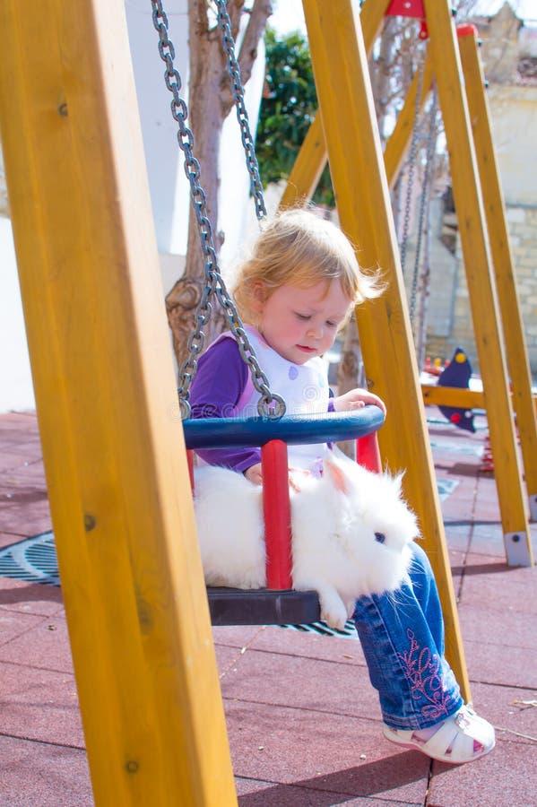 Niña y conejo en oscilaciones foto de archivo libre de regalías