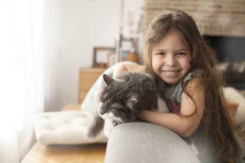 Niña y gato en casa en el sofá Un niño feliz y un animal doméstico Copie el espacio fotografía de archivo