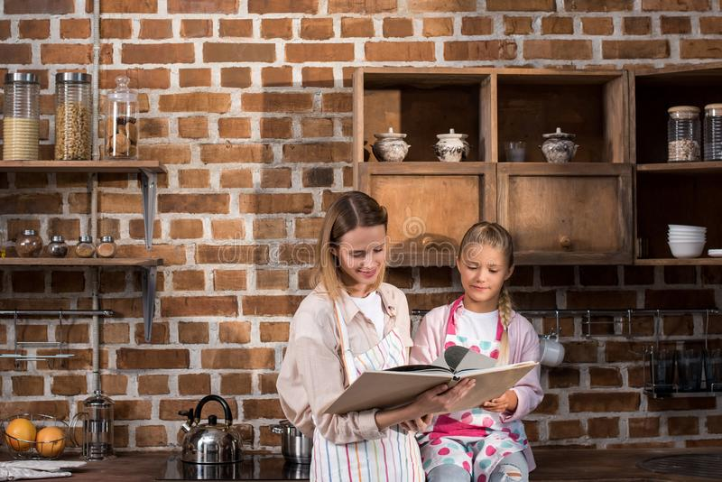 niña y madre en delantales que leen el libro de cocina junto imagenes de archivo