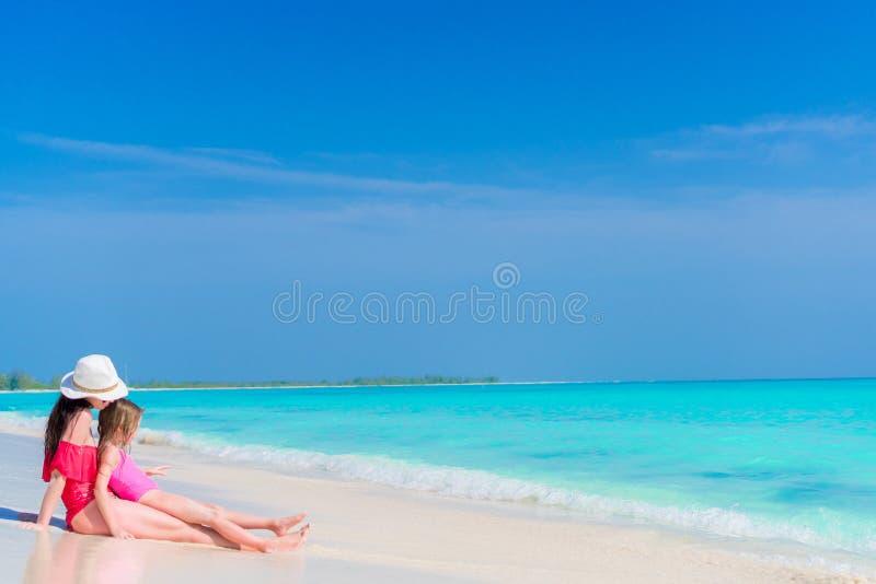 Niña y madre joven en la playa tropical que se sienta en agua poco profunda imagen de archivo