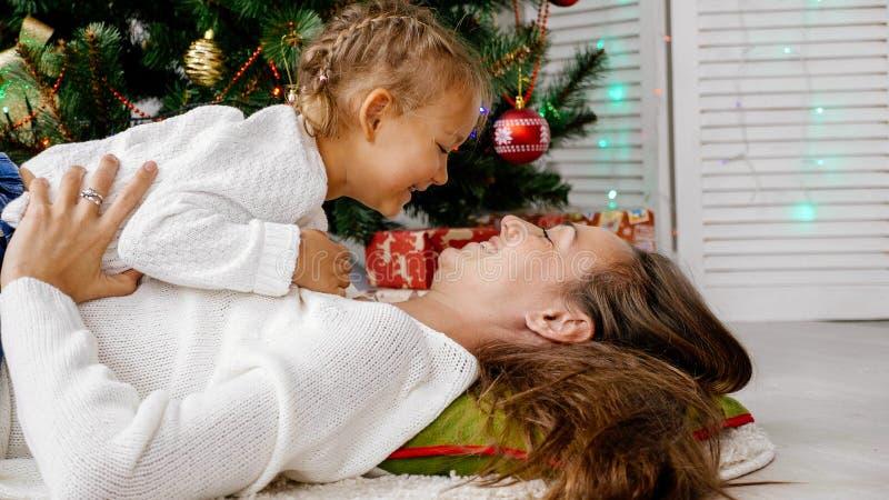 Niña y madre que abrazan dentro con el árbol de navidad en el fondo fotografía de archivo libre de regalías