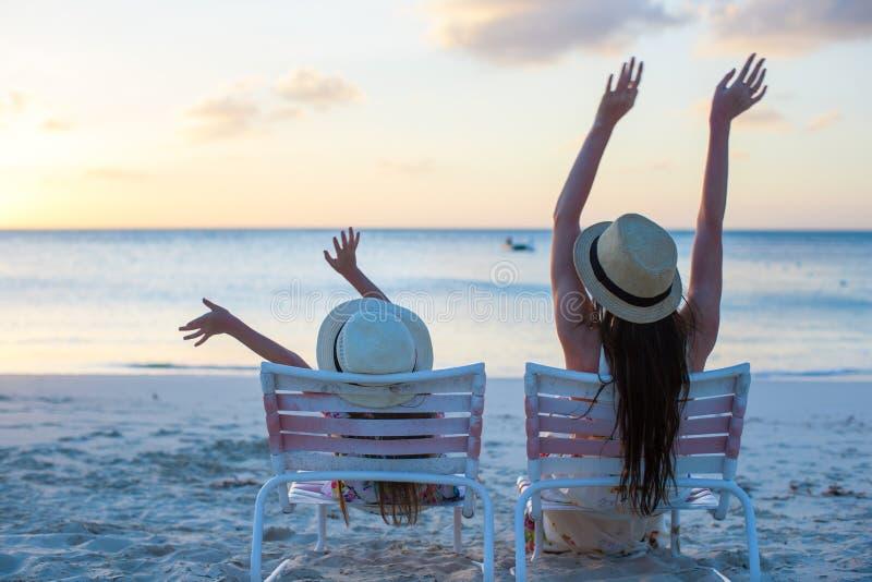 Niña y madre que se sientan en sillas de playa en imagen de archivo