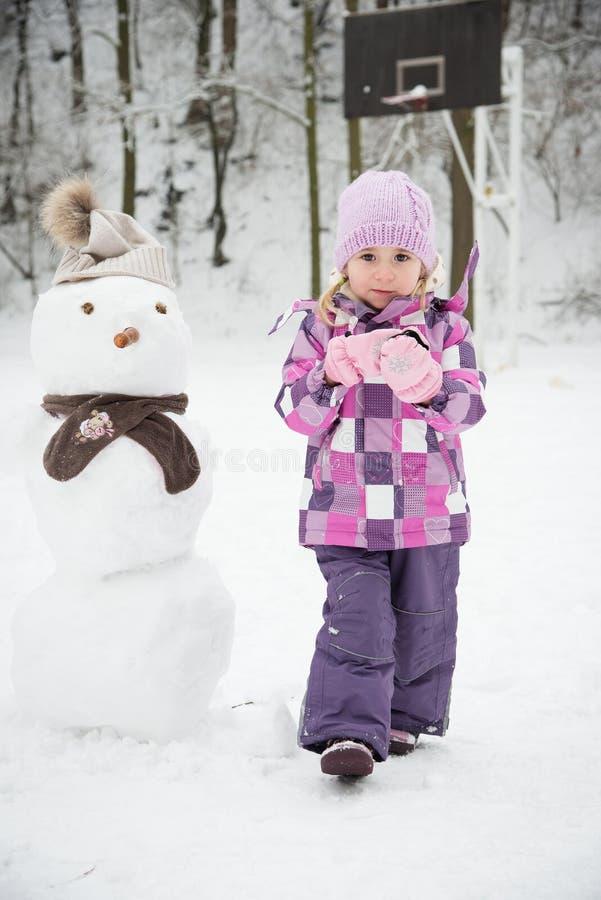 Niña y muñeco de nieve foto de archivo