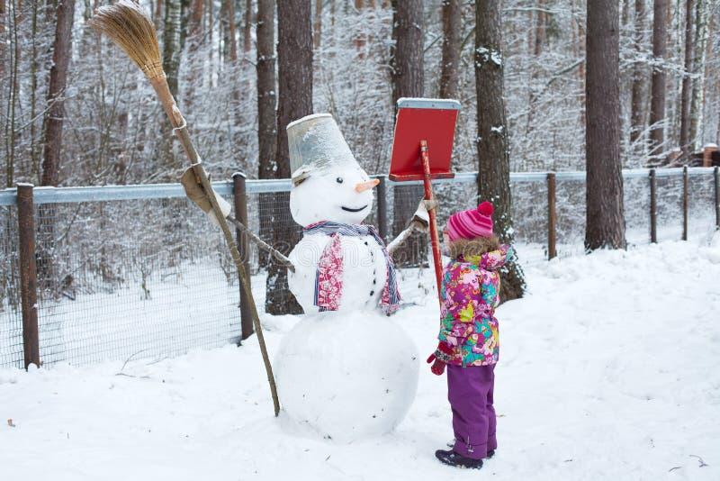 Niña y muñeco de nieve imagenes de archivo