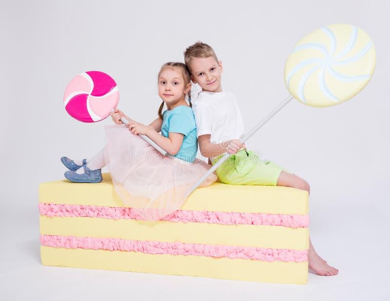 Niña y muchacho lindos con la torta y las piruletas grandes sobre blanco imagen de archivo
