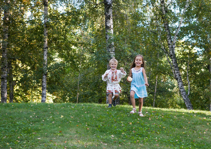 Niña y muchacho que corren de la colina imagen de archivo libre de regalías