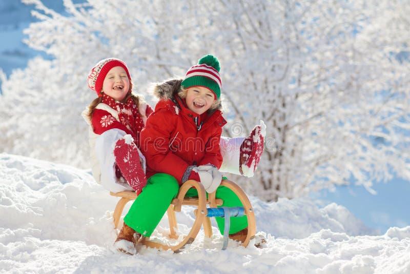 Niña y muchacho que disfrutan de paseo del trineo El sledding del niño Niño del niño que monta un trineo Juego de niños al aire l fotos de archivo libres de regalías