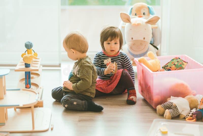 Niña y muchacho que juegan con los juguetes por el hogar imagenes de archivo