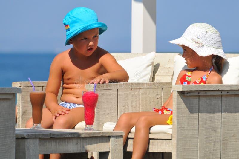 Niña y muchacho que se sientan en la piscina y la bebida foto de archivo