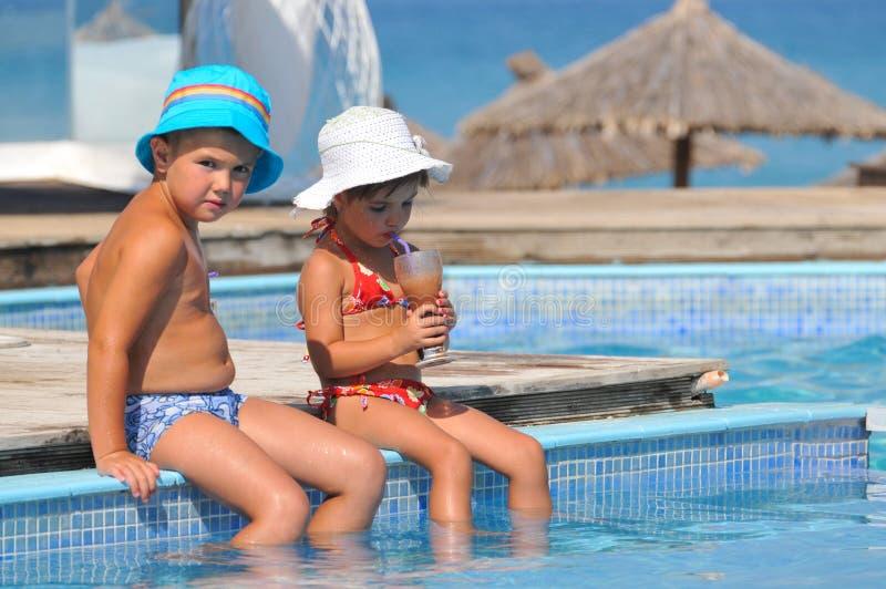 Niña y muchacho que se sientan en la piscina y la bebida imágenes de archivo libres de regalías
