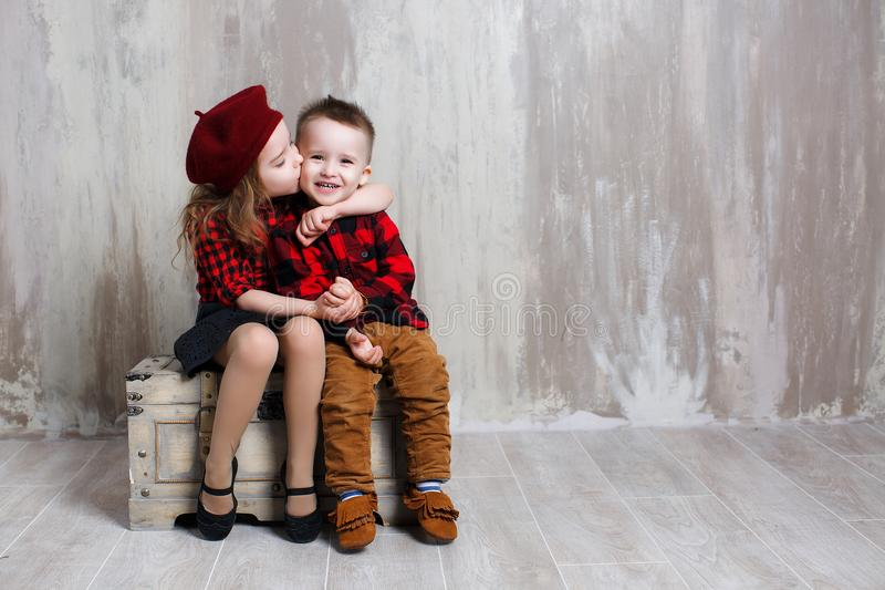 Niña y muchacho que se sientan en un pecho viejo en estudio en un fondo gris foto de archivo libre de regalías