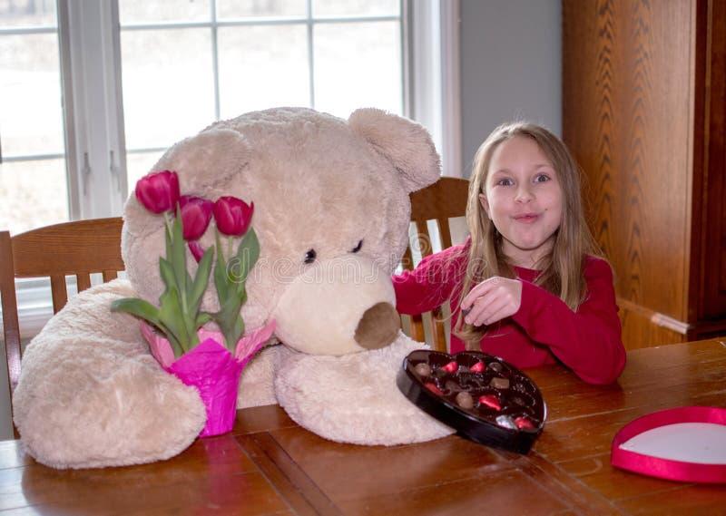 Niña y oso de peluche comparten regalos del día de San Valentín fotos de archivo libres de regalías