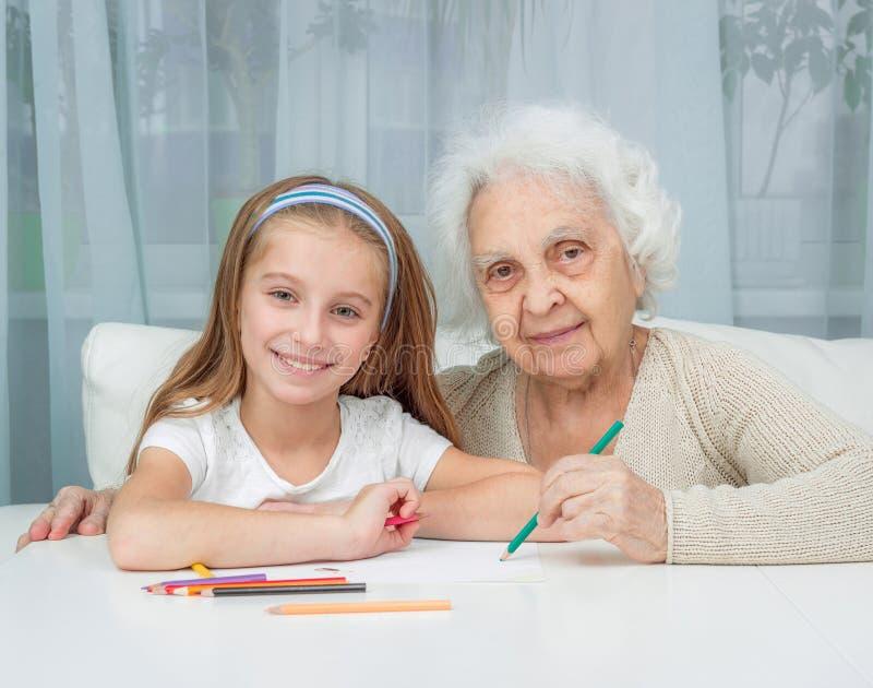 Niña y su dibujo de la abuela con foto de archivo libre de regalías