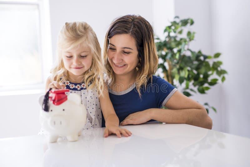 Niña y su madre que insertan el dinero en la hucha fotos de archivo
