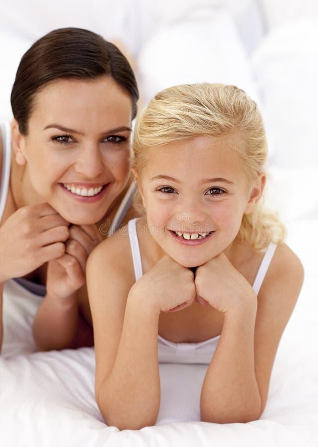 Niña y su madre que mienten en cama fotografía de archivo libre de regalías