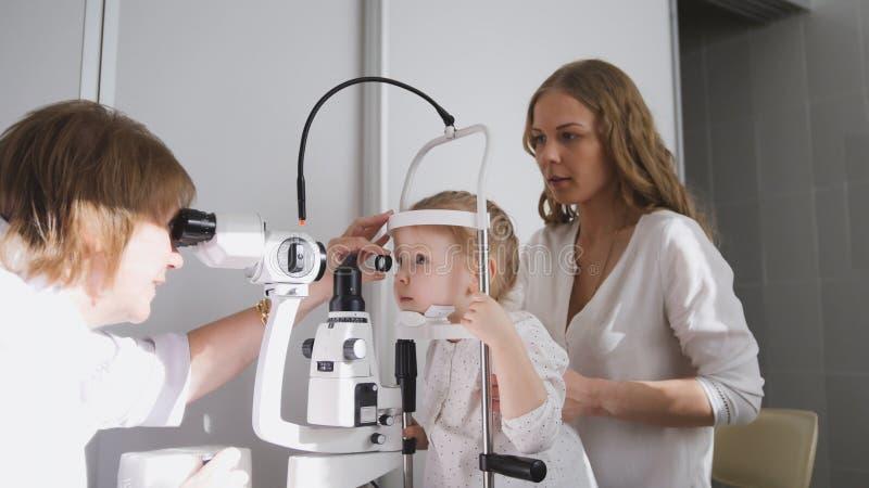 Niña y su mamá en oftalmología - optometrista que comprueba la visión del ` s del pequeño niño imagenes de archivo