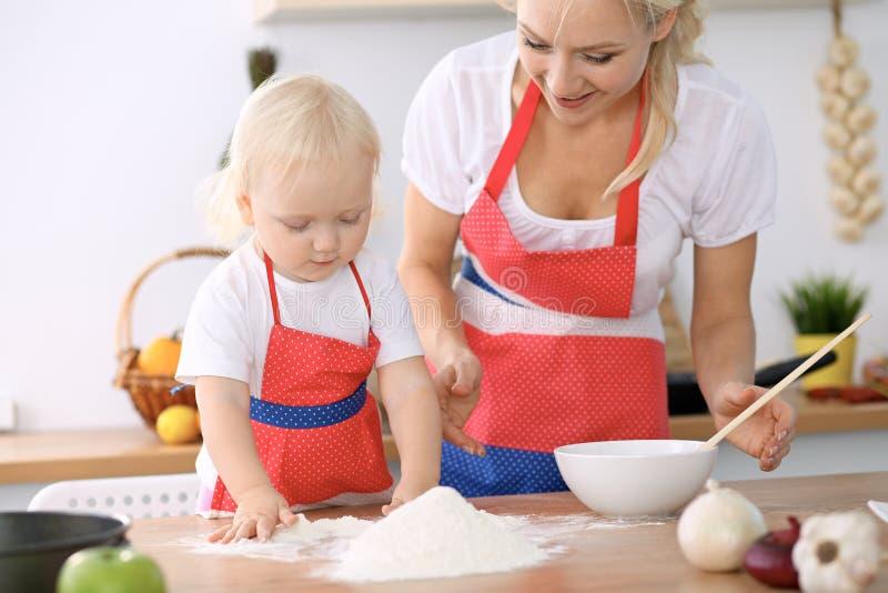 Niña y su mamá rubia en los delantales rojos que juegan y que ríen mientras que amasa la pasta en cocina Pastr hecho en casa fotos de archivo