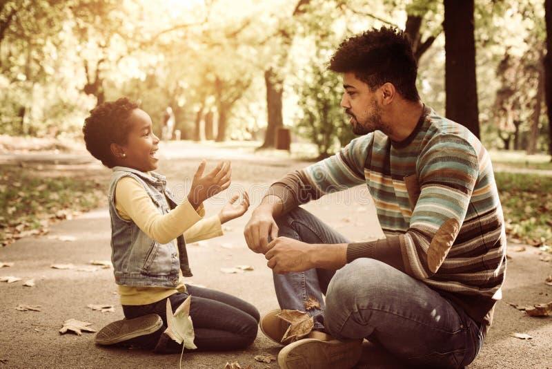 niña y su padre que se sientan en el camino en parque y imagen de archivo libre de regalías