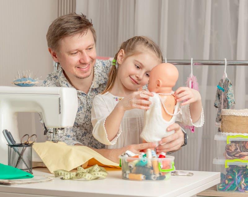 Niña y su papá en un taller de costura fotos de archivo
