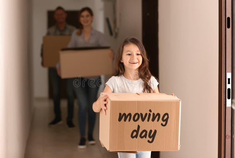 Niña y sus padres con las cajas de cartón dentro El trasladarse al nuevo apartamento imágenes de archivo libres de regalías