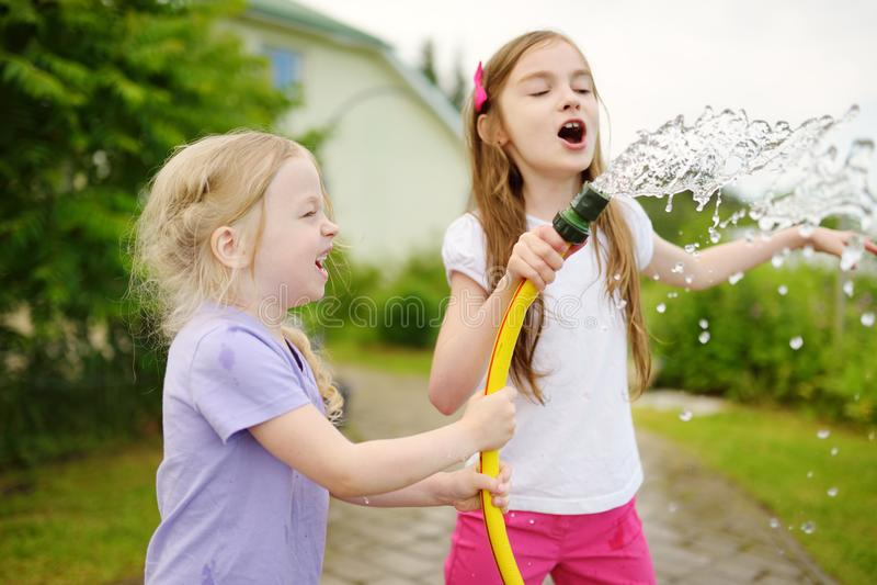 Niñas adorables que juegan con una manguera de jardín en día de verano caliente fotos de archivo libres de regalías