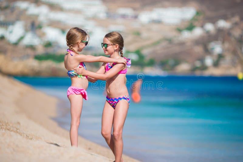 Niñas adorables que se divierten durante vacaciones de la playa Dos niños junto en las vacaciones griegas fotos de archivo libres de regalías