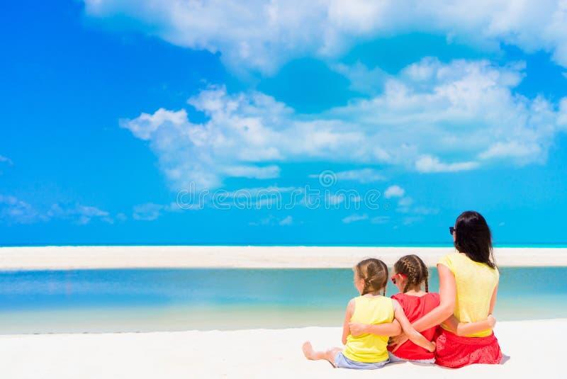Niñas adorables y madre joven en la playa blanca imagen de archivo