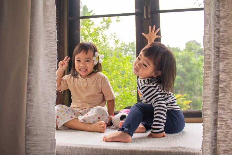 Niñas asiáticas felices hicieron un gesto encantador para tomar fotos en la habitación. Día de relajación familiar imagen de archivo libre de regalías