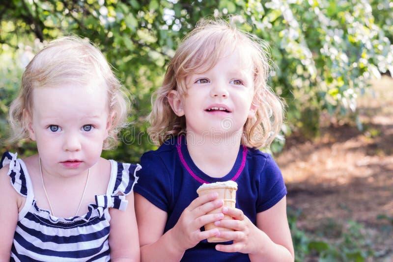 Niñas bonitas (hermanas) comiendo el helado en el verano fotografía de archivo libre de regalías