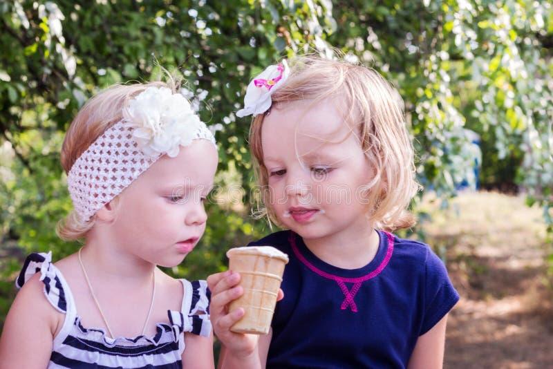 Niñas bonitas (hermanas) comiendo el helado en el verano fotos de archivo libres de regalías