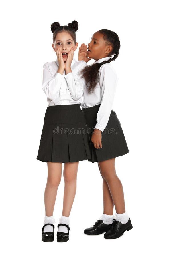 Niñas con uniforme escolar chismeando sobre los antecedentes foto de archivo