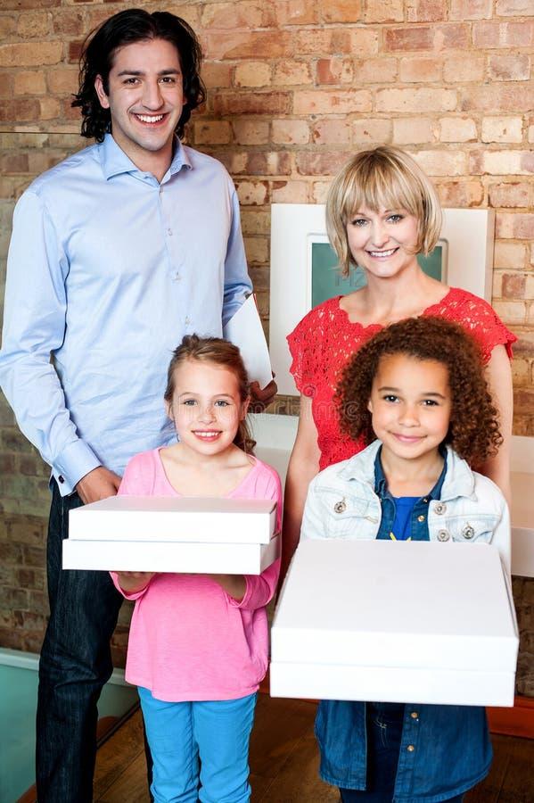 Niñas hermosas que sostienen las cajas de la pizza fotografía de archivo