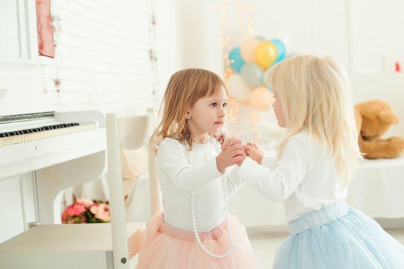Niñas lindas en los vestidos que juegan junto en un cuarto ligero Concepto del feliz cumpleaños imagenes de archivo