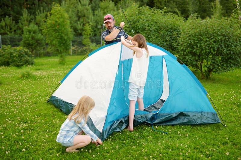 Niñas lindas que ayudan a su padre a poner una tienda en un sitio para acampar Forma de vida activa, fin de semana recreativo de  imágenes de archivo libres de regalías