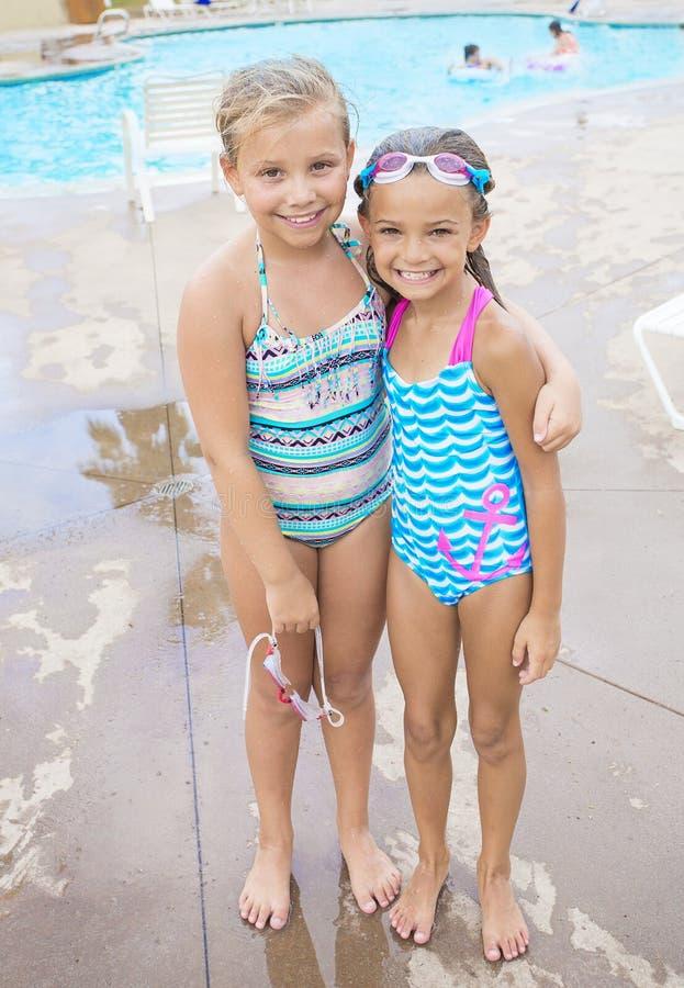 Niñas lindas que juegan en la piscina imagen de archivo