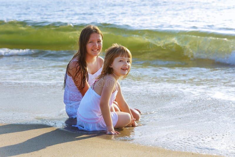 Niñas lindas que juegan en la playa junto durante vacaciones de verano fotografía de archivo