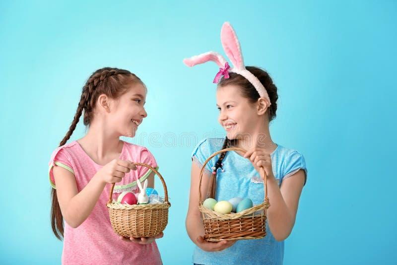 Niñas lindas que sostienen cestas de mimbre con los huevos de Pascua en fondo del color fotos de archivo