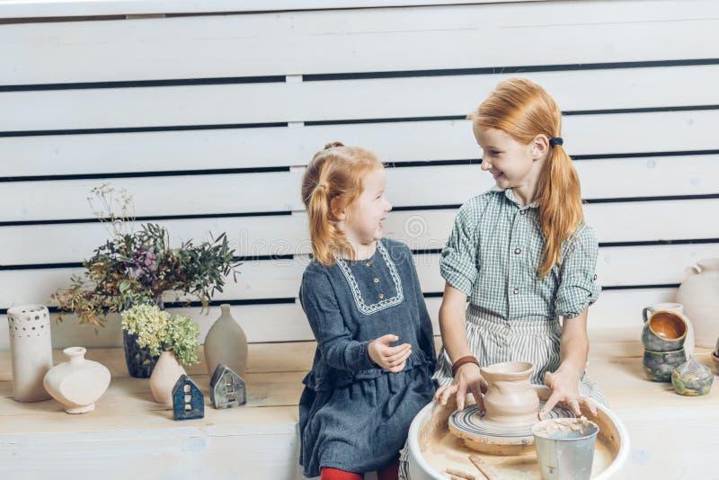 Niñas preciosas que hablan el uno al otro mientras que hace la jarra en la rueda de la cerámica fotos de archivo libres de regalías