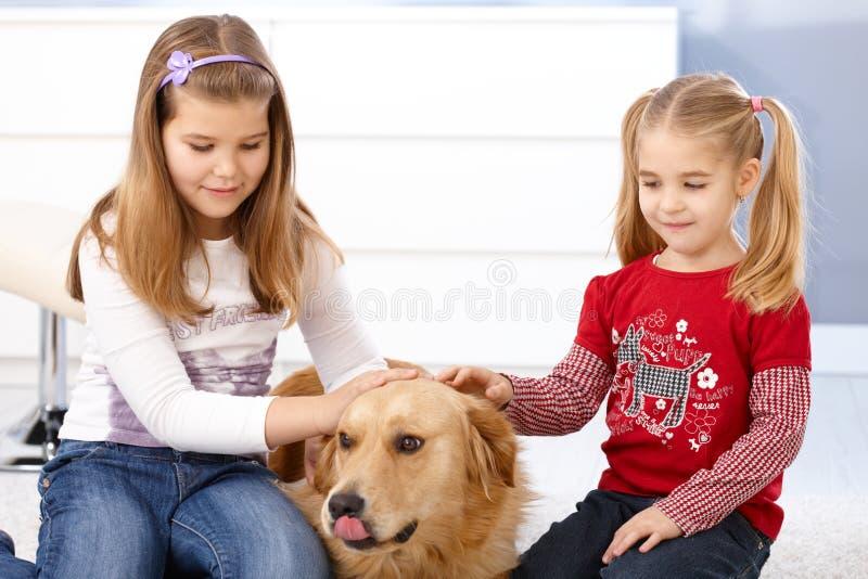 Niñas que frotan ligeramente la sonrisa del perro foto de archivo libre de regalías