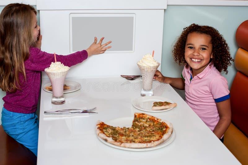 Niñas que gozan de la pizza en un restaurante imagen de archivo